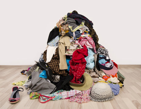 Close up on a big pile of clothes and accessories thrown on the floor. Untidy cluttered wardrobe with colorful clothes and accessories on the ground.