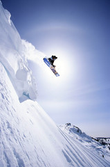 Snowboarder flying with mountains