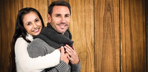 Composite image of smiling couple hugging and looking at camera