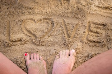 Conceptual Love Handwritten Text in Sand on a Beach in an Exotic Island with Lovely Couple Feet, Summertime