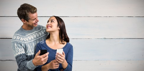 Composite image of happy romantic couple with mobile phone
