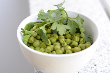 peas and parsley in white dishes