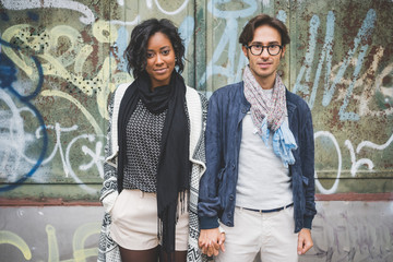 Portrait of couple standing against graffiti wall