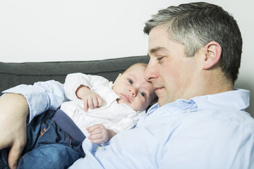 Father holding up baby girl lying on sofa, side view