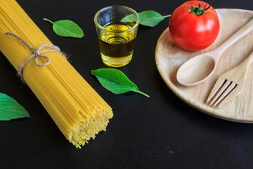 Spaghetti and tomatoes with basil on blackboard