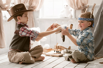 Boys as Indian and cowboy playing in her room