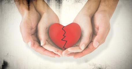 Composite image of couple holding broken heart in hands