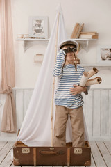 Boy in the image of sailor playing in her room