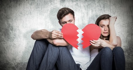 Composite image of young couple holding broken heart