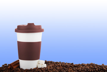 Takeaway ceramic cup and coffee beans on blue background