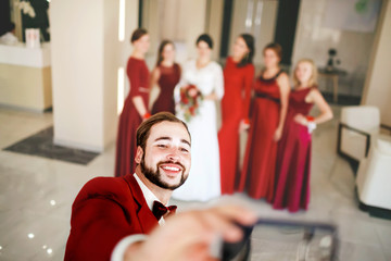 Groom makes selfie on background of bride with bridesmaids group photo.