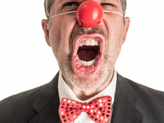 Closeup photograph of a man in a business suit with a red rubber nose and a sparkly red bow tie screaming toward the camera.