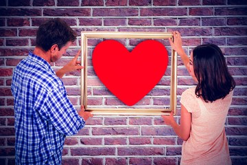 Composite image of couple holding picture frame