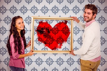 Composite image of smiling couple holding picture frame
