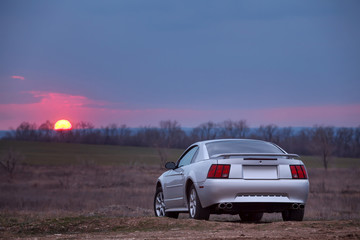 Wall Mural - Car stay on dirt road at sunset