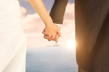 Composite image of close up of newlyweds holding their hands