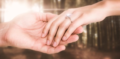 Composite image of close-up of couple holding hands