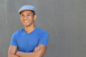 Portrait of a smiling Asian man in newsboy hat looking to camera