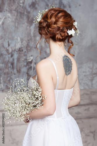 Young red haired bride in elegant wedding dress she stands with her young red haired bride in elegant wedding dress she stands with her back to mightylinksfo