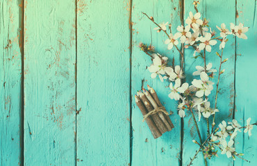 image of spring white cherry blossoms tree next to wooden colorful pencils on blue wooden table. vintage filtered image