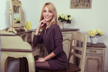 Beautiful young fashion 30-35 years blonde model in brown dress and black shoes and makeup and hairstyle and fair hair posing near the secretaire and looking at camera in provence design interior.