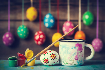 Painting Easter eggs and hanging colorful eggs on rustic wooden