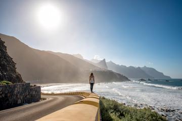 Woman walking near the mountain road