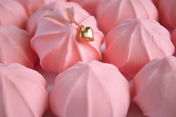 A golden heart pendent on pink strawberry meringues background