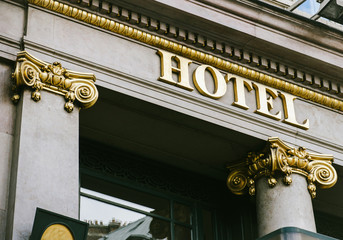 Hotel word with golden letters on beautiful facade with golden columns