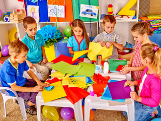 Group kids holding colored paper on craft lesson in kindergarten .