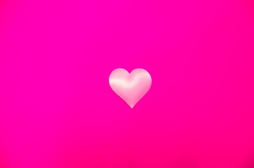 White love heart in the middle on a pink background, bright pink background with heart