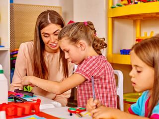 Teacher is teaching children how to make origami in kindergarten .