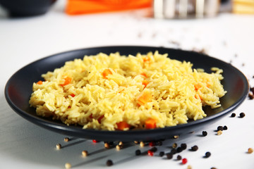 Stewed rice with a carrot on a black plate over white background, close up