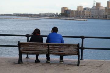 Coppia di innamorati seduti su una panchina del lungomare