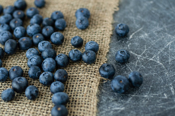 Scattered blueberries on jute tablecloth and scratched black background