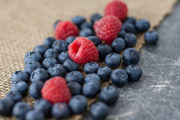 Blueberries and raspberries scattered on a jute cloth and chalkboard background