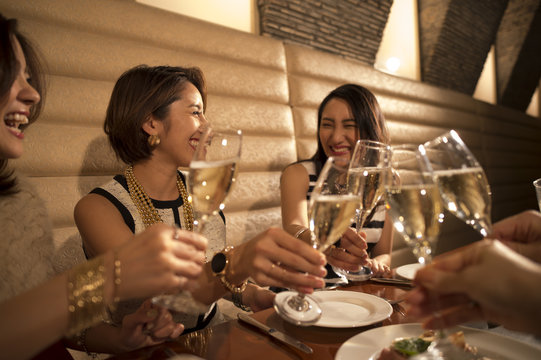 Women are toast with champagne in a luxurious restaurant