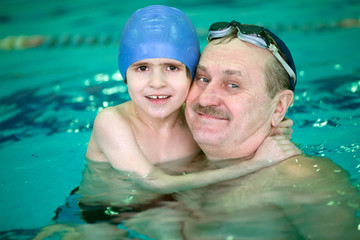grandfather with small boy in swimming pool