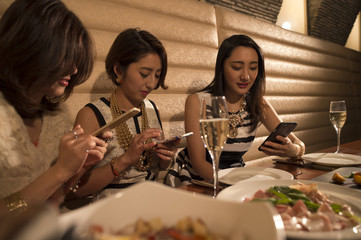 Three women are concentrated in the smart phone during a meal in the restaurant