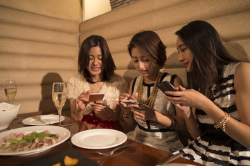 Three women are using a smartphone during a meal in the restaurant