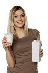 smiling young woman holding a glass of milk and Cardboard packaging