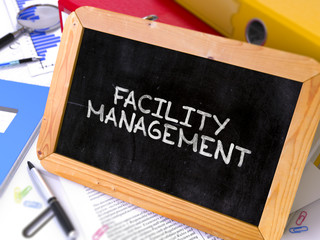 Facility Management - Chalkboard with Hand Drawn Text, Stack of Office Folders, Stationery, Reports on Blurred Background. Toned Image. 3D Render.
