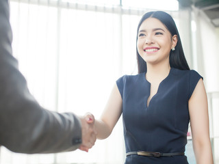 Smart and confident Asian businesswoman smiling and shaking hand
