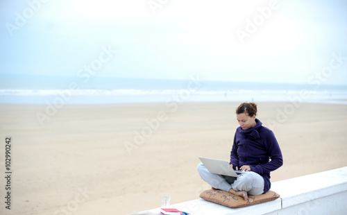 46f90c59d1cc Frau mit modernem Arbeitsplatz arbeitet am Strand am laptop