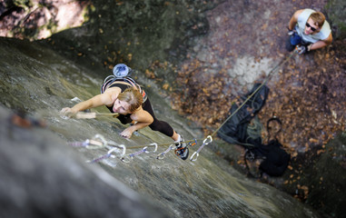 Athletic young woman rock climbing with carbines and rope