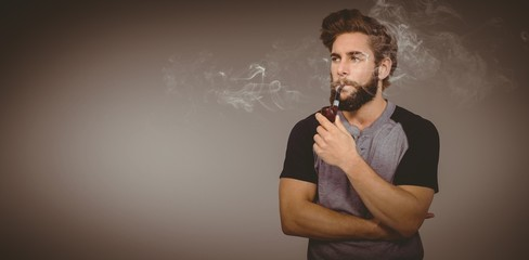 Composite image of confident hipster smoking pipe