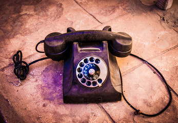 Retro black old vintage telephone on table with brick grunge bac