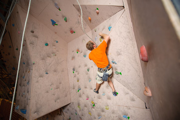 Young man climbing on practical wall in gym, bouldering.