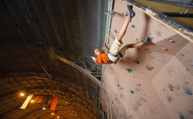 Young man climbing on practical wall in gym, bouldering. Giving