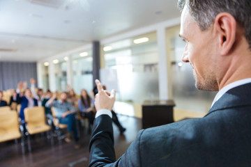 Speaker pointing to audience on business conference